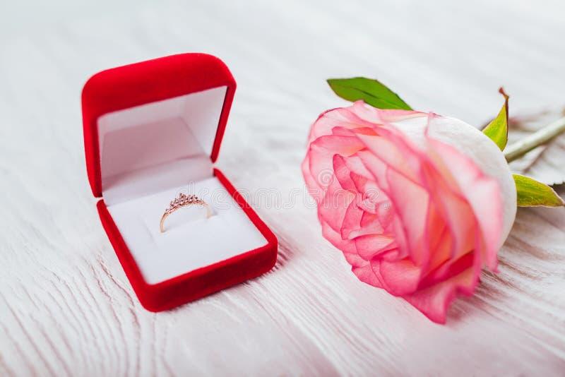 Gouden ring met diamanten in rood giftdoos en boeket van rozen Heden voor de Dag van Valentijnskaarten royalty-vrije stock foto's