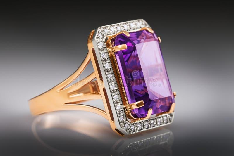 Gouden ring met een groot amethist en zirkonen op een gradi?ntachtergrond royalty-vrije stock foto's