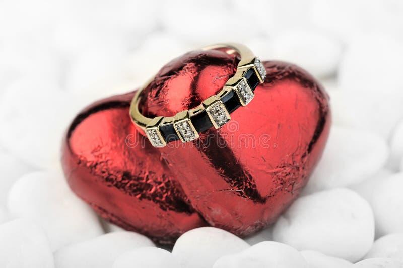 Gouden ring met saffieren & diamanten op rode harten stock foto's