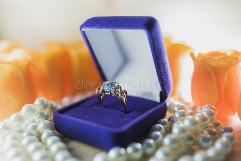 Gouden ring met topaas in een giftdoos op parels stock afbeelding