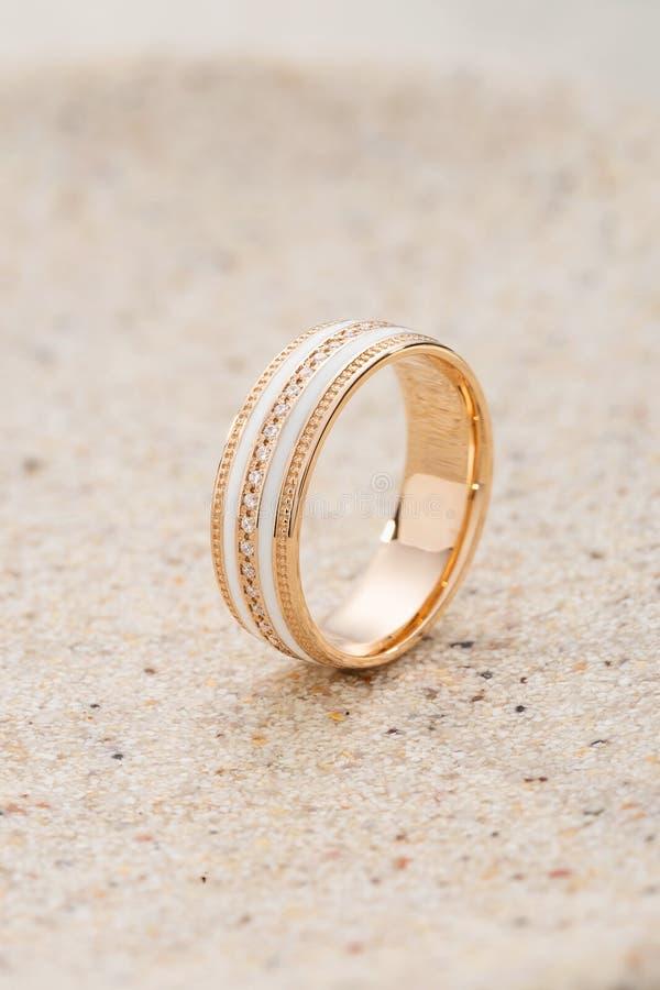 Gouden ring met wit email en diamanten op beige zandachtergrond stock afbeelding