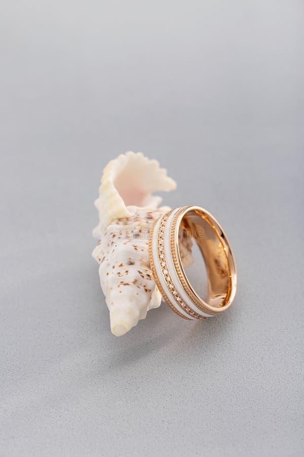 Gouden ring met wit email en diamanten op grijze achtergrond met zeeschelp stock foto's