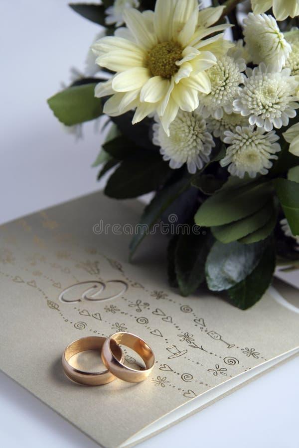 Gouden ringen, uitnodiging en bloemen stock fotografie