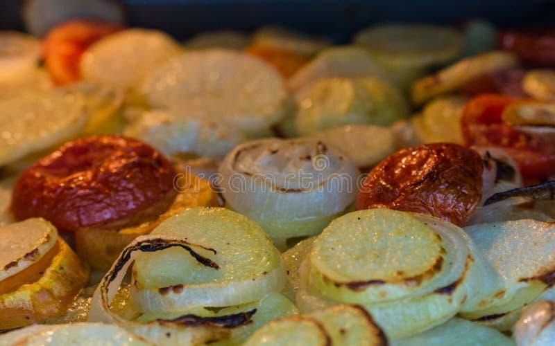 Gouden rode aardappels warme tomaten en uien in een oven stock foto's