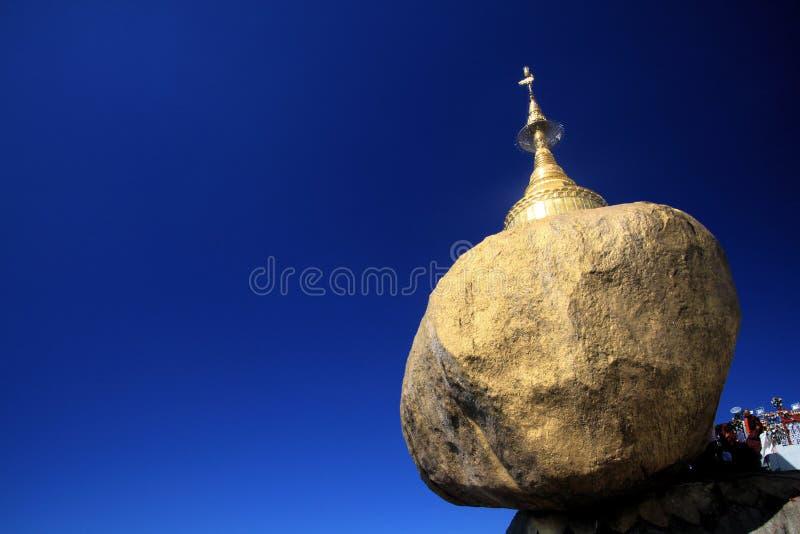 Gouden Rots die tegen blauwe hemel tegenover elkaar stellen Goud het geschilderde kei in evenwicht brengen op de rand van steile  royalty-vrije stock foto's