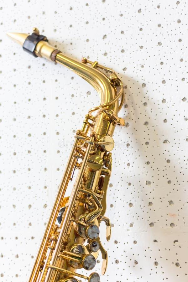 Gouden saxofoon op witte en blauwe muurachtergrond stock foto