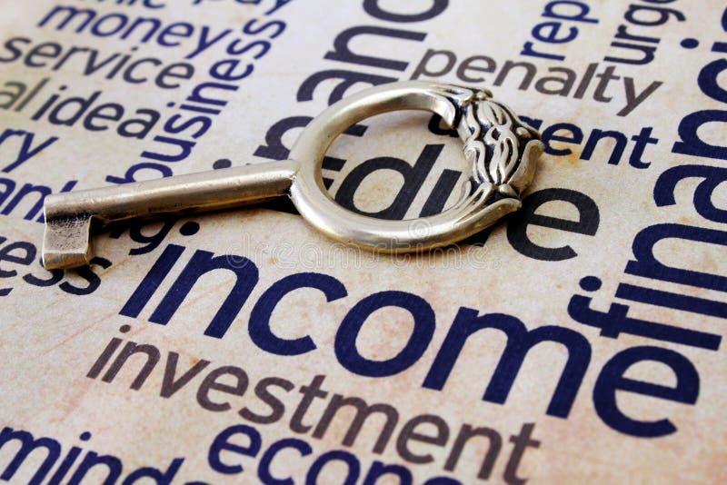 Gouden sleutel op inkomenstekst stock foto's