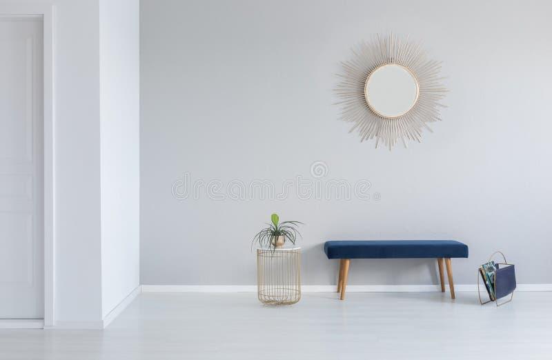 Gouden spiegel op de muur boven blauwe bank in minimaal leeg halbinnenland met installatie stock fotografie