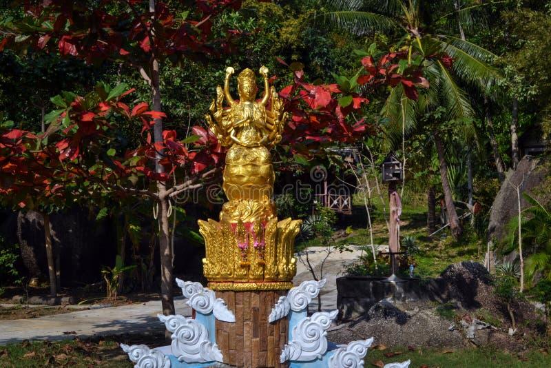 Gouden standbeeld van de godin in de bloeiende tuin Boeddhistische tempel bij een klein Thais dorp royalty-vrije stock foto