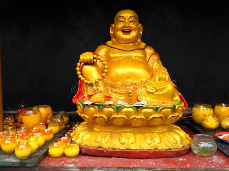 Gouden standbeeld van vette lachende Boedha met boeddhistische rozentuinzitting op een lotusbloem met rond het branden van kaarse stock afbeelding