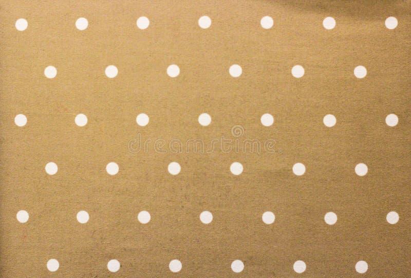 Gouden stof en een witte uiterst kleine stippenachtergrond stock afbeelding