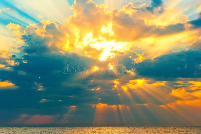 Gouden stralen van de zon die door de onweerswolken breken stock fotografie