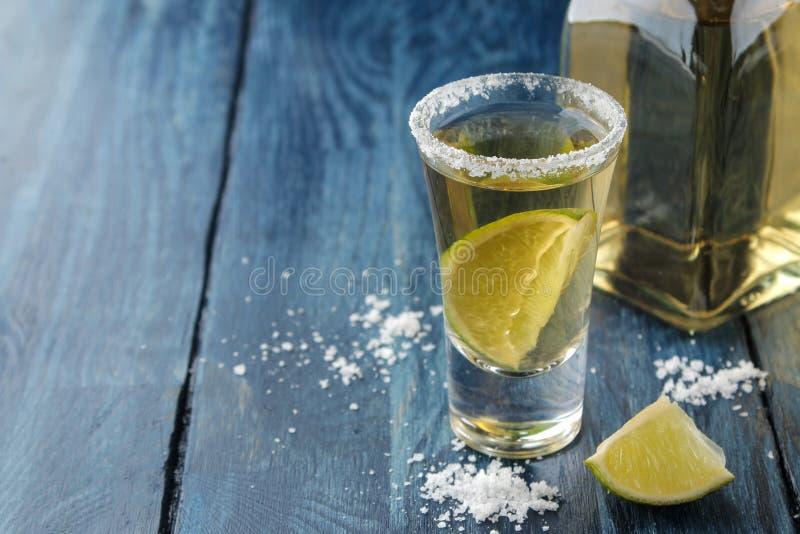 Gouden tequila in een glas met zout en kalk op een blauwe houten lijst Alcoholische dranken stock fotografie