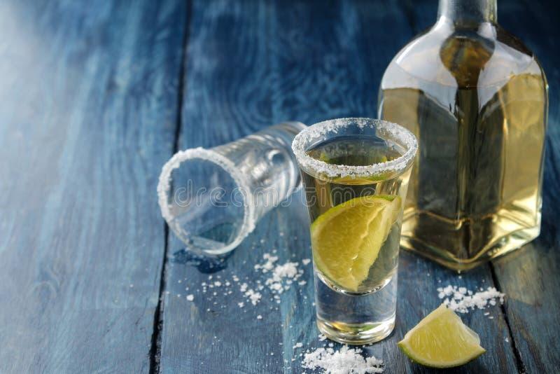 Gouden tequila in een glas met zout en kalk op een blauwe houten lijst Alcoholische dranken stock foto