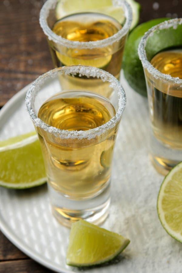 Gouden tequila in een glas met zout en kalk op een bruine houten lijst Alcoholische dranken stock afbeelding