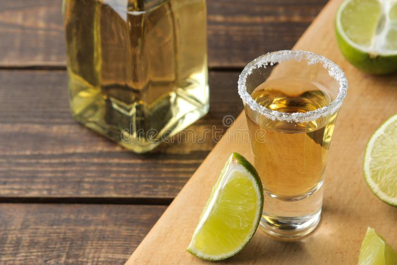 Gouden tequila in een glas met zout en kalk op een bruine houten lijst Alcoholische dranken stock afbeeldingen