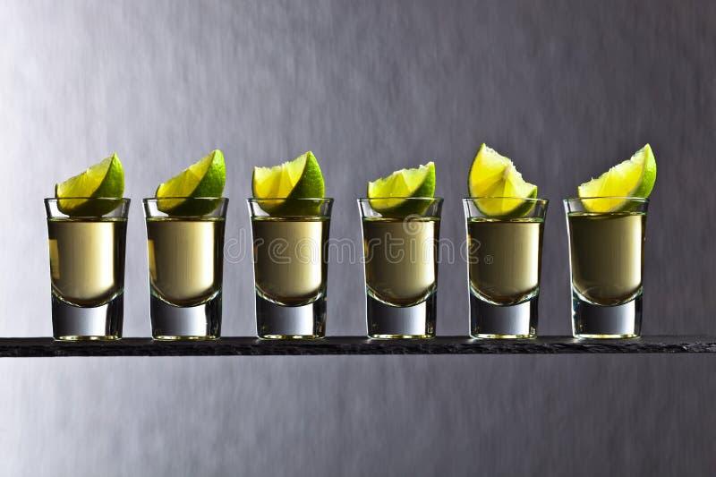 Gouden tequila met kalk stock foto's