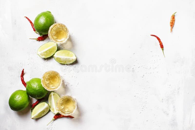 Gouden tequila met kalk op witte drankachtergrond, hoogste mening stock foto's