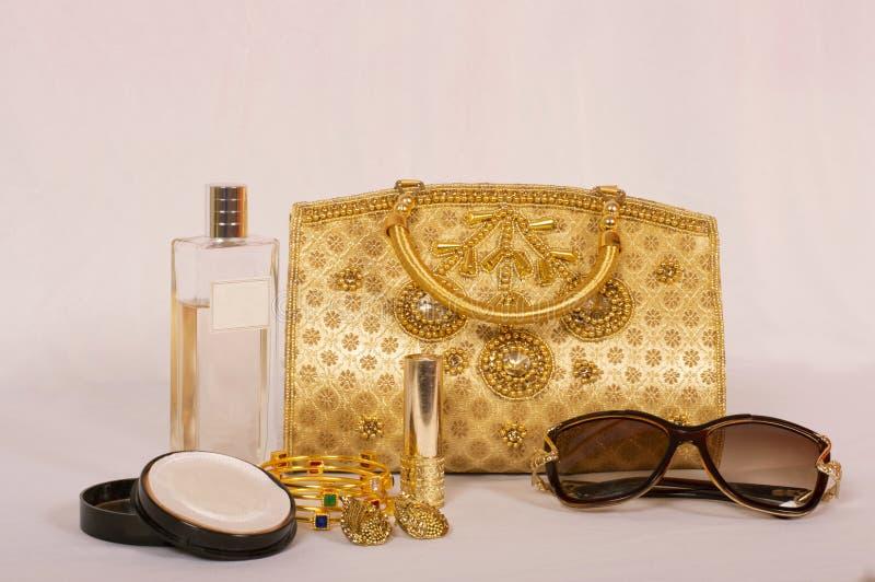 Gouden traditionele handtasbeurs met schoonheidsmiddelen en de toebehoren van vrouwen royalty-vrije stock afbeeldingen