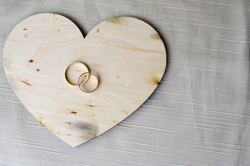 Gouden trouwringen op een houten hart Heldere, schitterende, betoverende, modieuze, dure die harten van hout met versieringen FO  stock foto