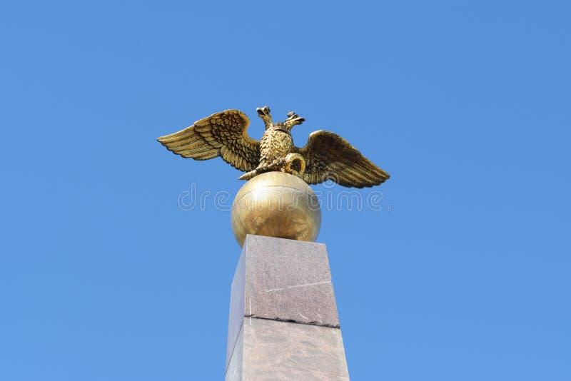 Gouden twee-geleid adelaarsbeeldhouwwerk op obelisk stock afbeeldingen