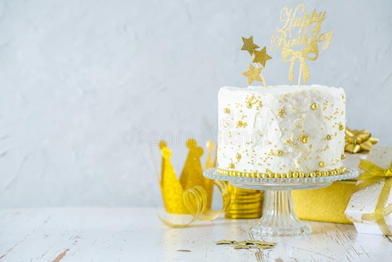 Gouden verjaardagsconcept - de cake, stelt, decoratie voor stock afbeelding