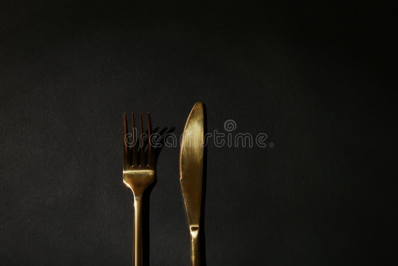 Gouden vork en mes op zwarte achtergrond Ruimte voor tekst stock foto's