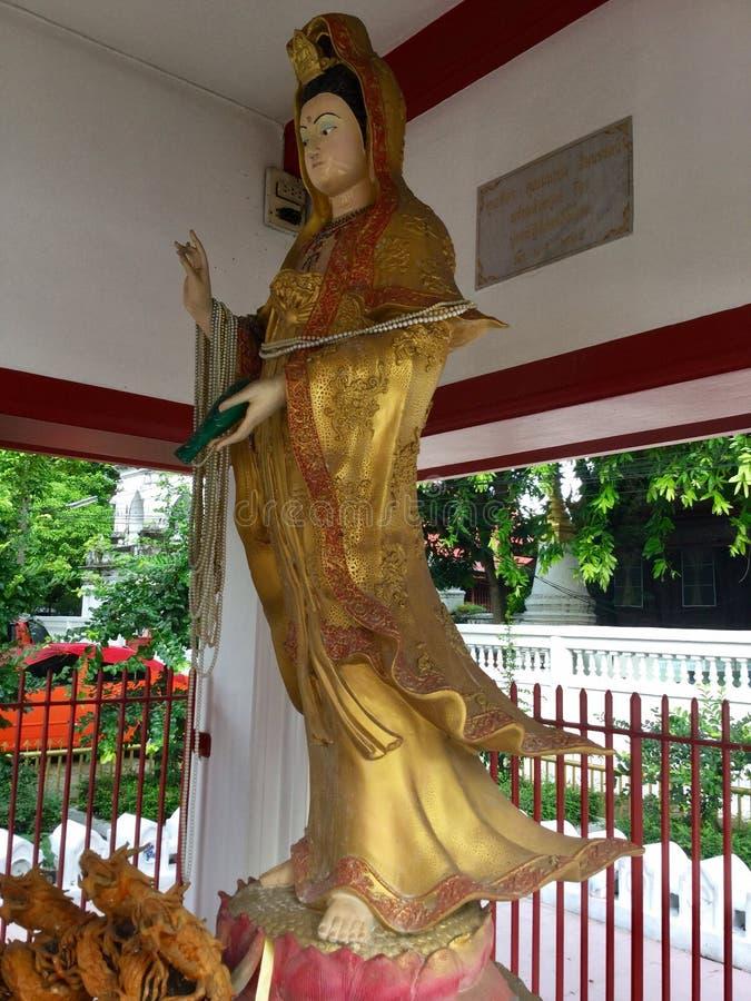 Gouden vrouwenbeeldhouwwerk dichtbij Wat tamachat, Thaise tempel bangkok stock afbeelding
