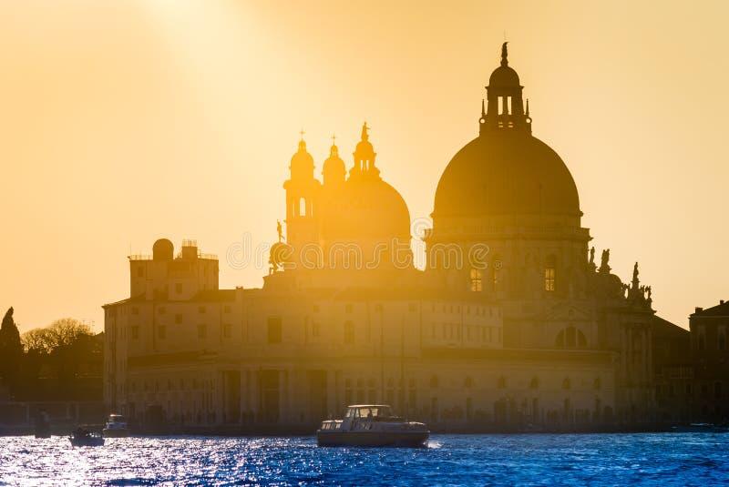 Gouden zonsondergang achter de Santa Maria della Salute-kerk in Venetië stock foto