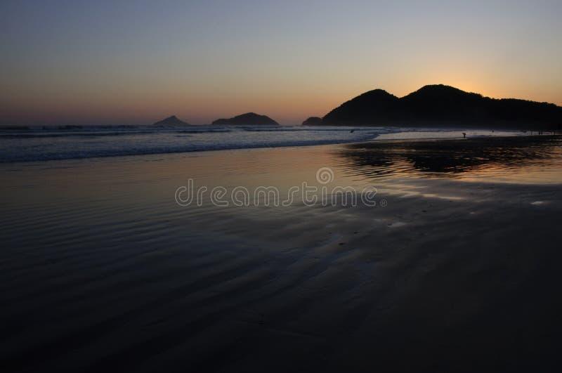 Gouden zonsondergang bij een tropisch strand stock foto's