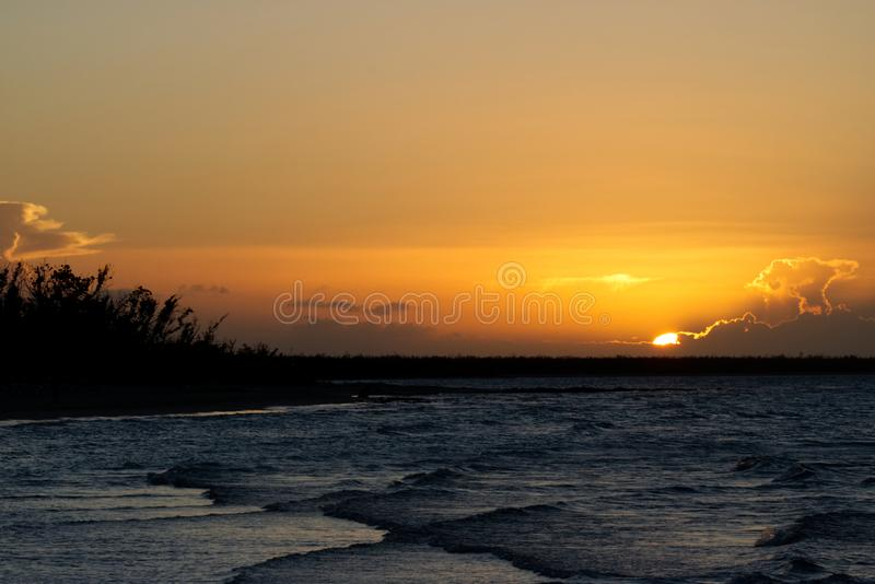 Gouden zonsondergang in Caribbeans met uiterst kleine golven stock afbeelding
