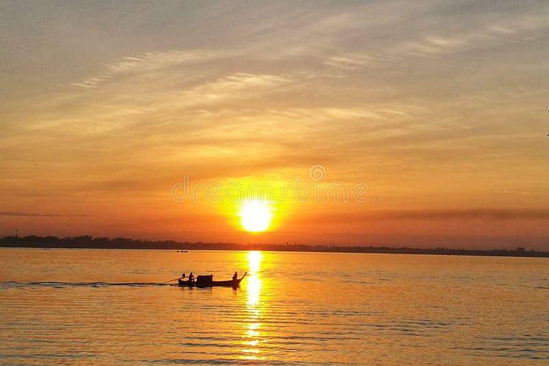 Gouden zonsondergang en bezinning over overzees met vissersboot stock fotografie