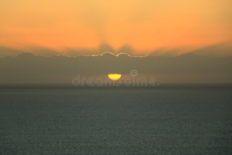 Gouden zonsondergang lichte onderbrekingen door de hemel met wolken over de oceaan royalty-vrije stock foto