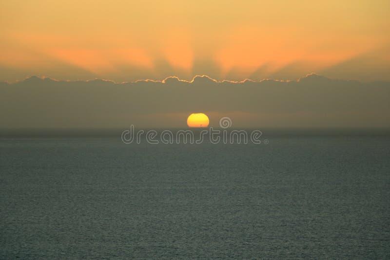 Gouden zonsondergang lichte onderbrekingen door de hemel met wolken over de oceaan stock afbeelding