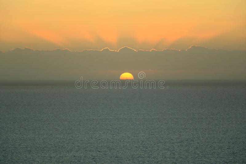 Gouden zonsondergang lichte onderbrekingen door de hemel met wolken over de oceaan stock foto's