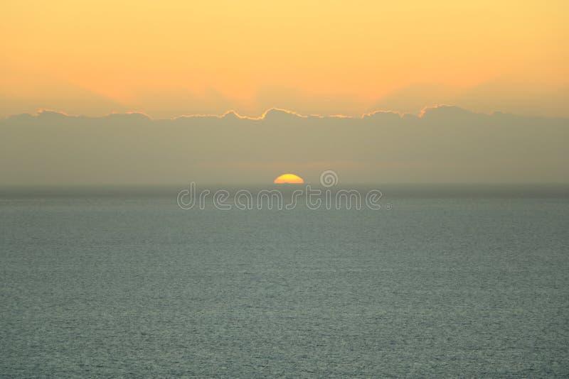 Gouden zonsondergang lichte onderbrekingen door de hemel met wolken over de oceaan royalty-vrije stock foto's