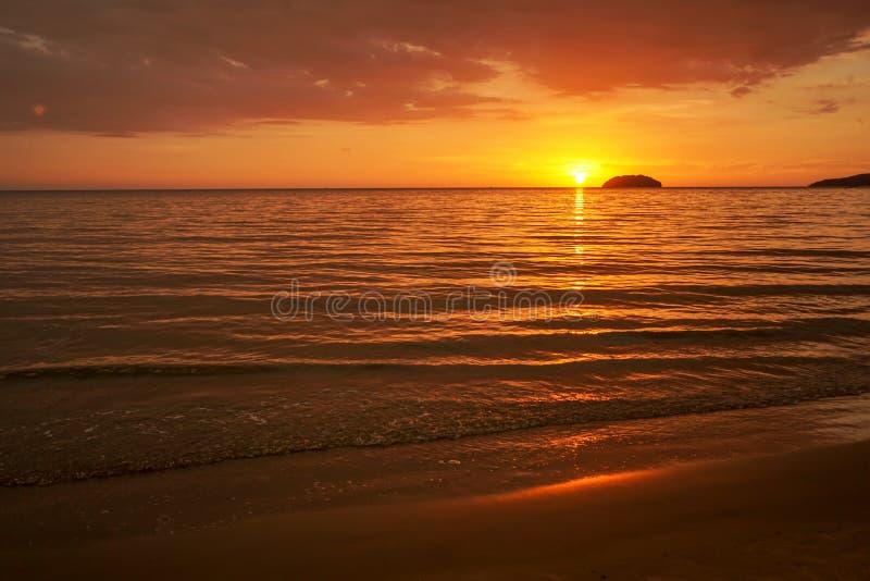 Gouden zonsondergang op het strand met avondgloed Het overzeese bezinningsrode licht als zonsopgang royalty-vrije stock foto