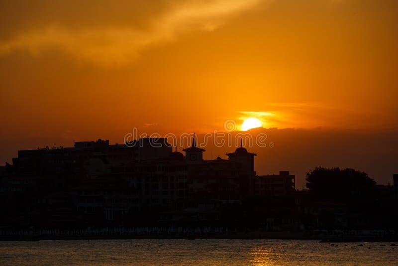 Gouden zonsondergang op het strand Silhouet van de stad Mooie architecort door het overzees op de achtergrond van de zonsondergan royalty-vrije stock foto