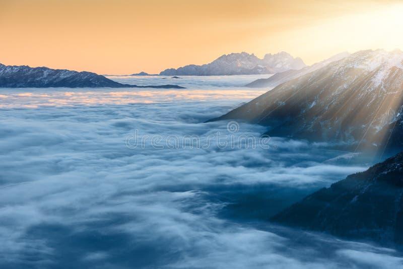 Gouden zonsondergang over wolken en bergpieken stock fotografie