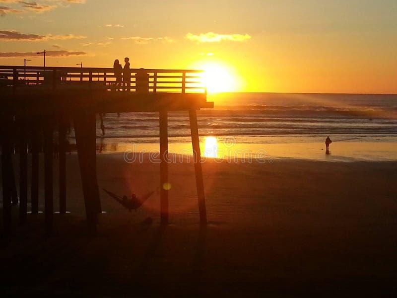 Gouden Zonsondergangmensen in silhouet bij Pismo-Strand stock foto
