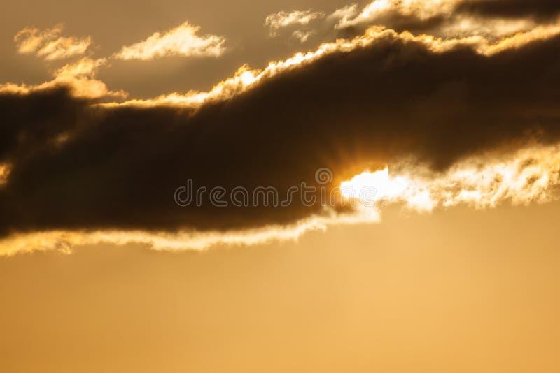 Gouden zonsondergangwolken met zon die door gluren royalty-vrije stock afbeeldingen