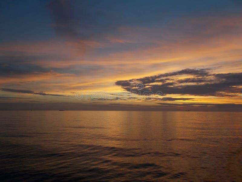 Gouden zonsopgang gouden dageraad over een overzeese vlotte oppervlakte royalty-vrije stock afbeelding