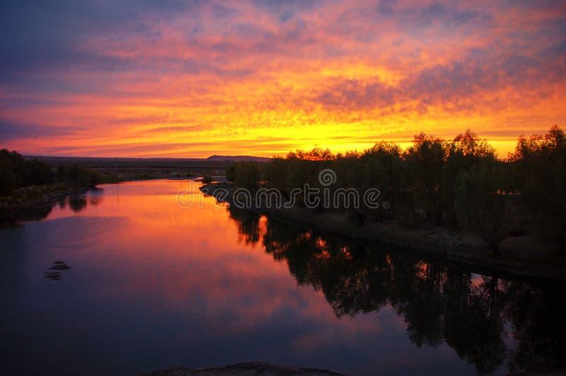 Gouden zonsopgang met kleurrijke vlammende wolken, het rode licht van de rivierbezinning als zonsondergang stock afbeeldingen