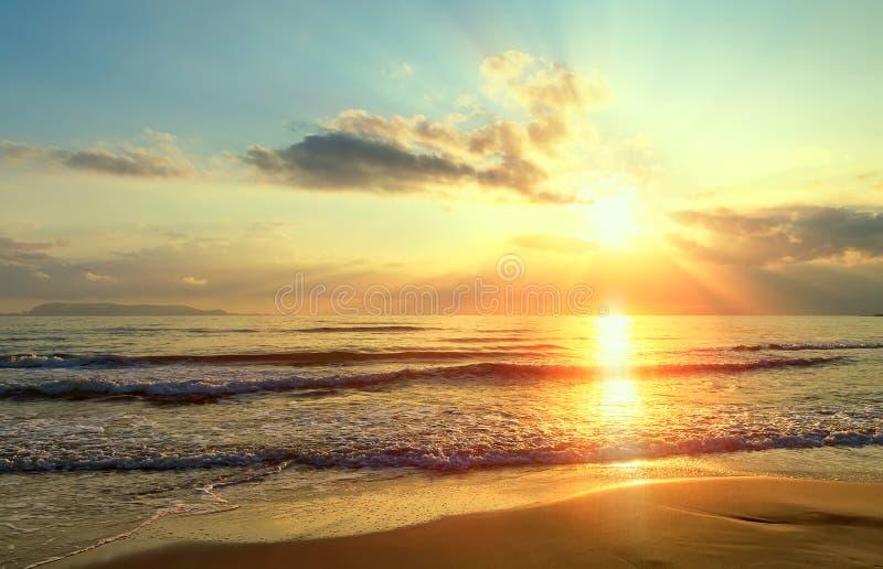 Gouden zonsopgangzonsondergang over de overzeese oceaangolven Rijken in donkere wolken, stralen van licht stock afbeelding