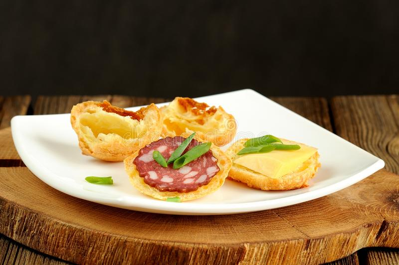 Gougeres with cheese and sausage on white plate stock photo