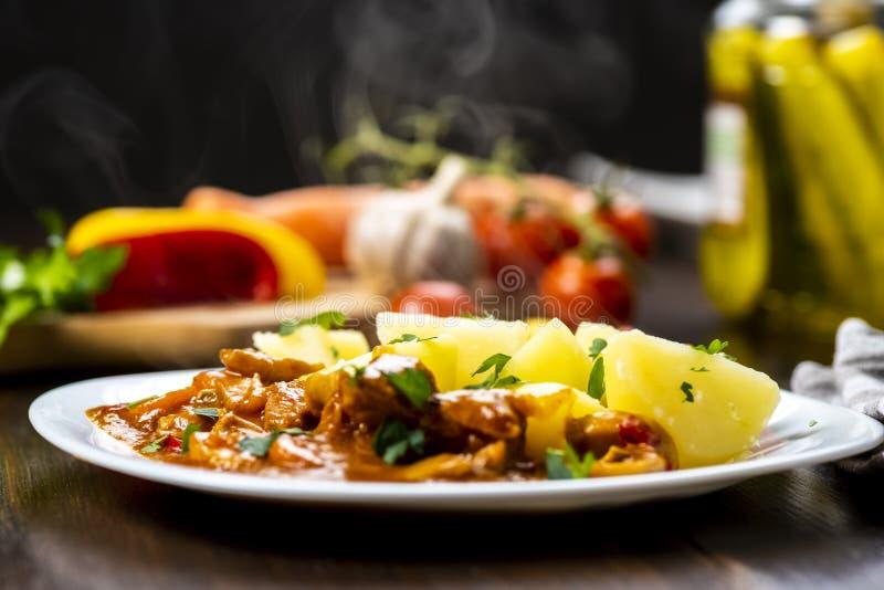 Goulash χοιρινού κρέατος που εξυπηρετείται με τις βρασμένες πατάτες στοκ εικόνα με δικαίωμα ελεύθερης χρήσης