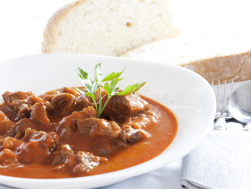 Goulash. Stew served in white bowl. Bread in the background stock images