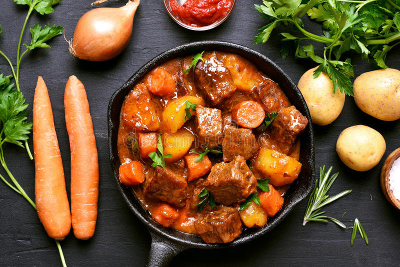 Goulash, beef stew. And ingredients on dark background, top view royalty free stock images