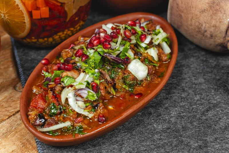 goulash from beef, veal and vegetables - tomato, cabbage, potatoes, served with greens and pomegranate seeds royalty free stock image
