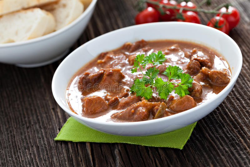 Goulash. In a bowl with bread royalty free stock photo